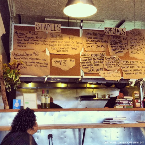 The daily menu above the open kitchen counter with bar seating.