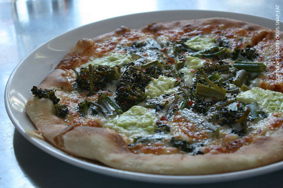Broccoli rabe pizza with basil pesto, cheese and chili flakes