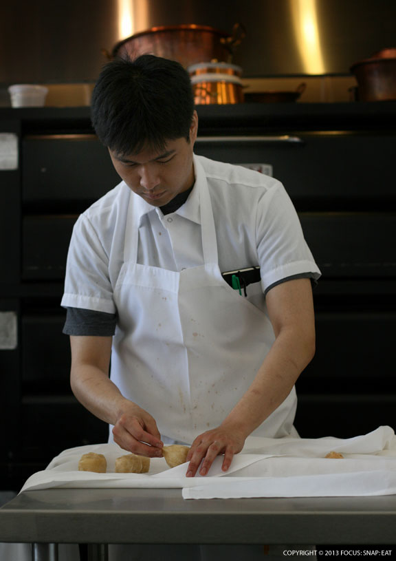 I sat in front of this guy who was focused on making some kind of pastry where he pinched a ball from the roll of dough.