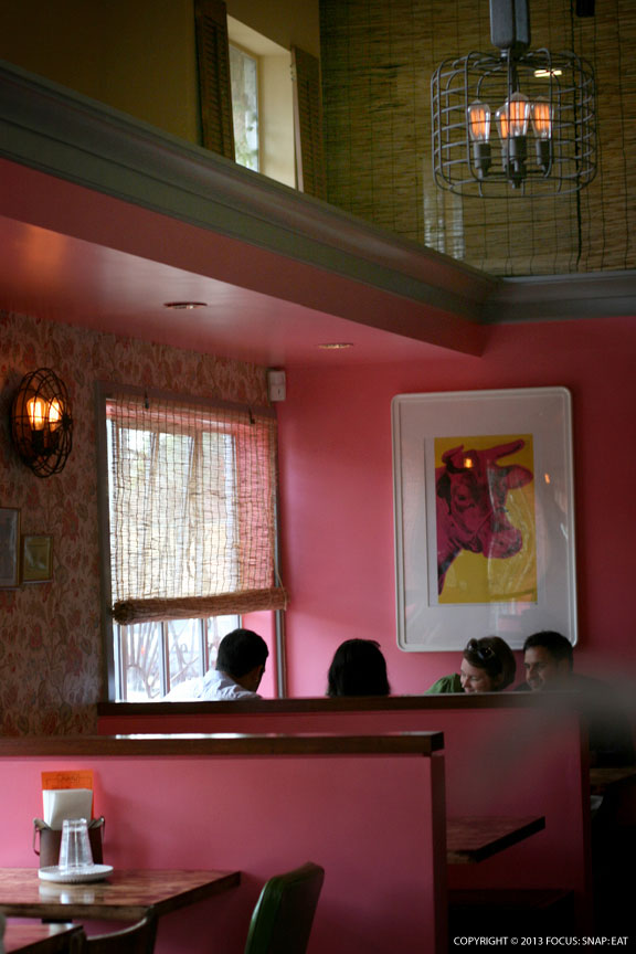 Bright pink is a theme to the restaurant, offset by a British-style wallpaper and old pictures of families in Mumbai