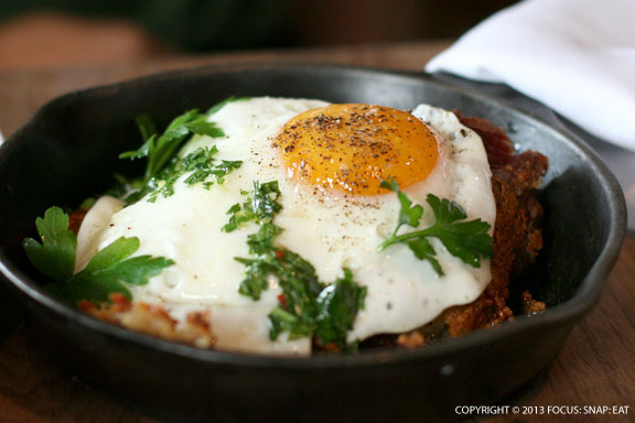 Corned beef cheek hash with fried egg, sherry vinegar, gremolata ($11)