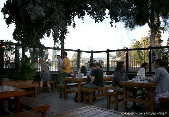 One side of the patio has seating facing the partial view of Lake Merritt
