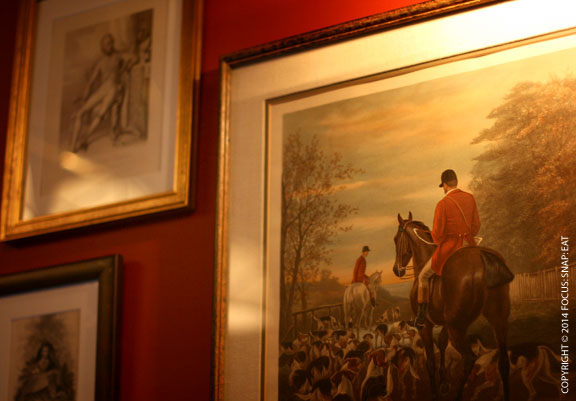 British-inspired paintings on the wall giving the room a hunting lodge vibe