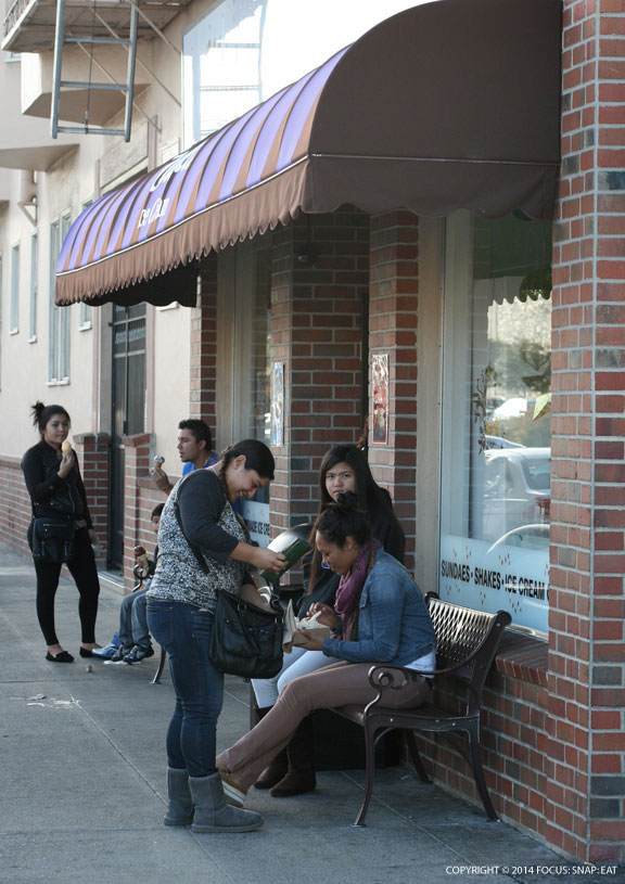 Customers enjoying their ice cream in front of the store