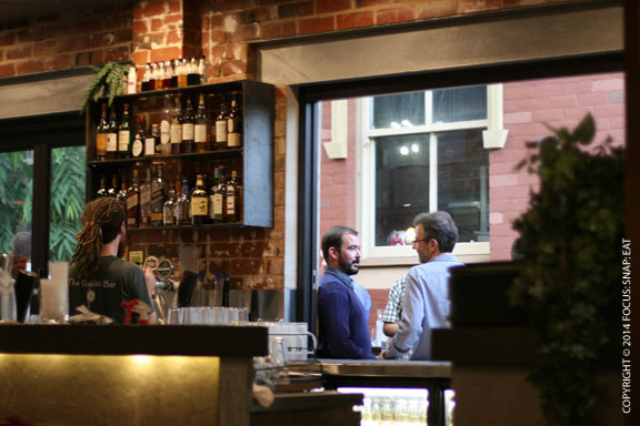 Looking out from the inside bar to the guests enjoying drinks in the outdoor space.
