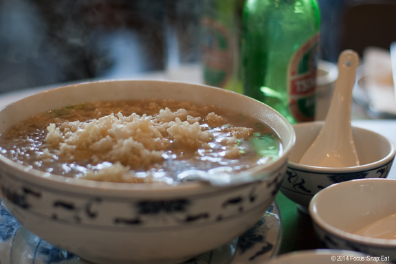 Sizzling rice soup, a clear broth with chicken, shrimp, vegetables, all topped with puffed rice, which is added at the table (medium order, $9.95)