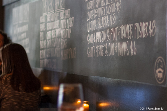 Chalkboard with daily specials on the bar side of the room, adding to the tavern feel.