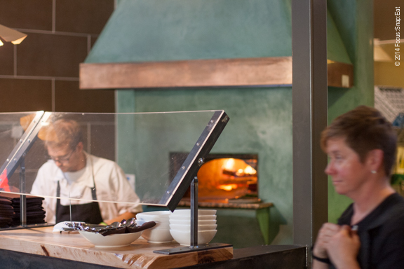 The wood-fire oven, and trying to get out of the frame on the bottom right is Chef/Co-owner Jen Biesty.