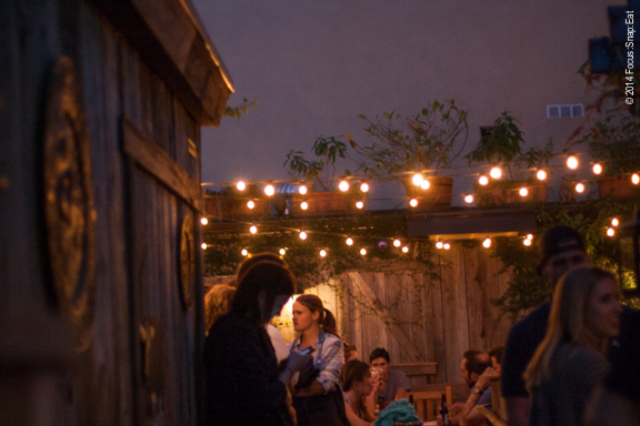 Diners enjoying drinks and food on a warm night at the restaurant's patio area