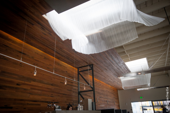 Bar Agricole's award-winning design is highlighted by wave-like art sculptures around the sky lights.