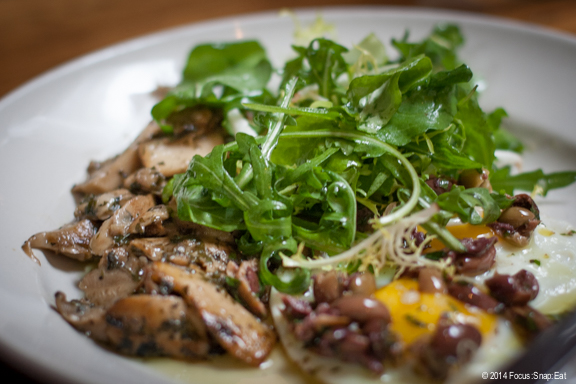 Two fried eggs with matsutake mushrooms, chopped olives and frisee salad ($14)