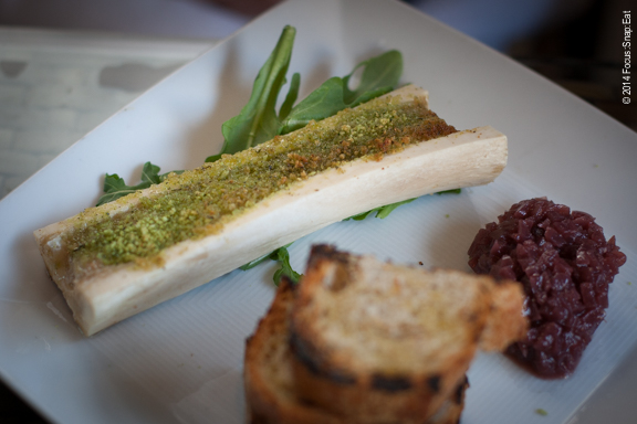 Parsley crusted bone marrow gives the bone marrow a green hue ($10) and is served with onion marmalade and grilled bread.