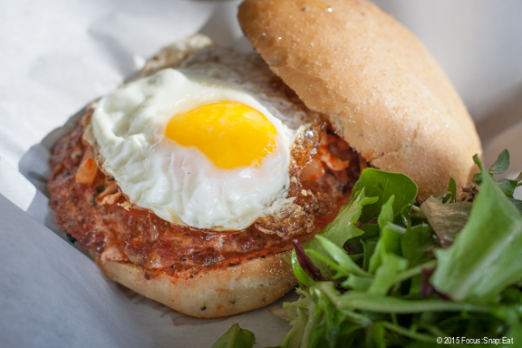 Hangover Special ($11) with breakfast sausage, kim chi relish and fried egg on a potato pepper bun.