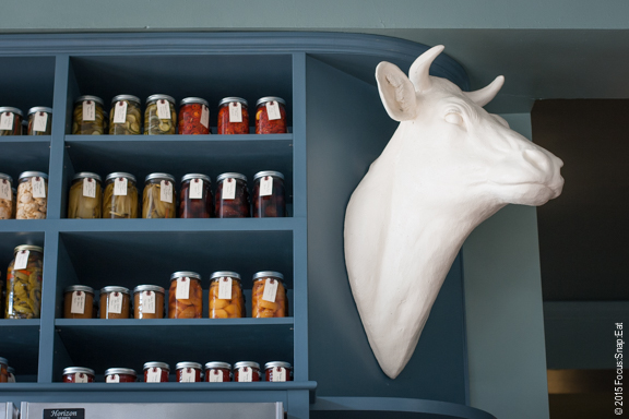 Pickled jars line the high shelves near a cow head.
