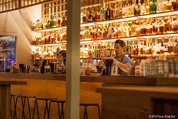 The large bar makes a statement with the shelves of backlit liquor bottles