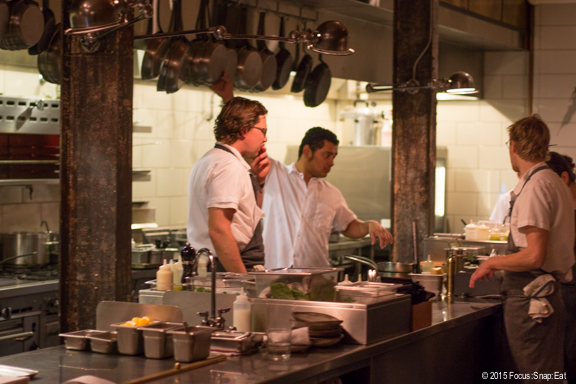 The chefs take a pause in the open kitchen before the next wave of orders come in.