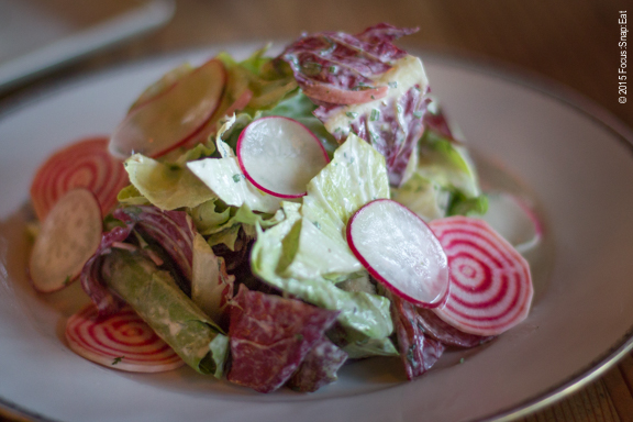 Perfect for the season: mixed chicories with creme fraiche, shaved chioggia beets, radishes and spearmint ($13)