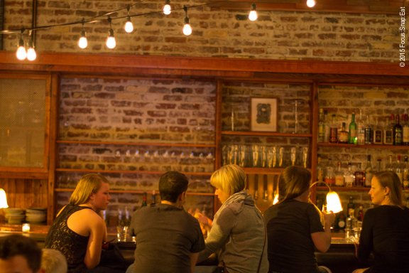 View of the bar with exposed bricks and string lights like a garden party