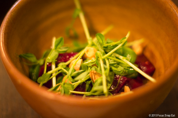 Side of grilled beets with snap peas and shoots, almonds