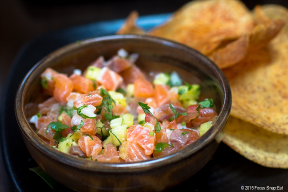 Salmon lomi lomi ($14) with added ingredients of Maui pineapple chunks and serrano chili, along with the traditional onions and tomato, served with taro root chips.