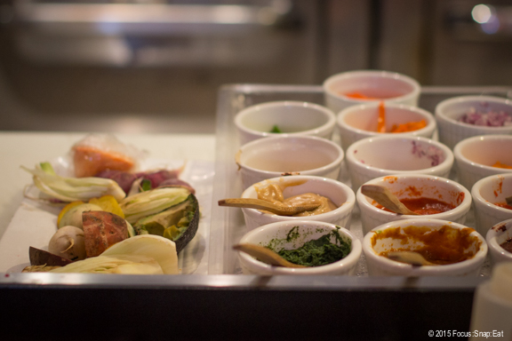 Sitting at the chef's counter, you get a bird's eye view of the cooking. Dishes with colorful ingredients ready to be combined into dinner for someone.