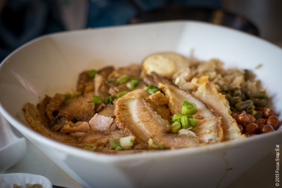 Large bowl of rice noodles topped with BBQ pork and crispy pork.