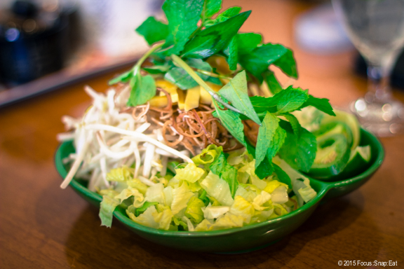 Plate of fresh herbs, bean sprouts, and other greens to mix with our soup noodles.