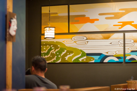 A colorful mural adorns a wall in the dining room