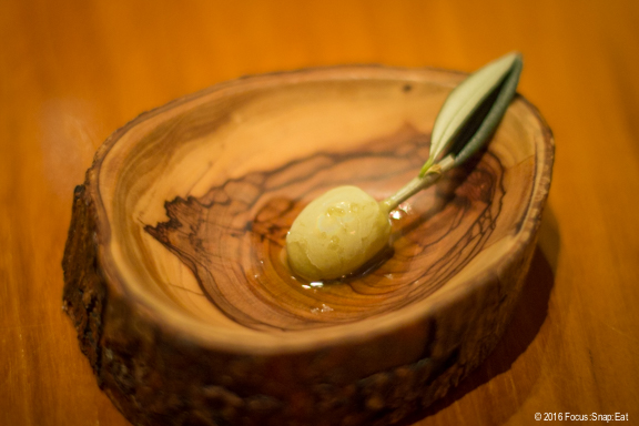 Pistachio sorbet in the shape of an olive served with olive oil.