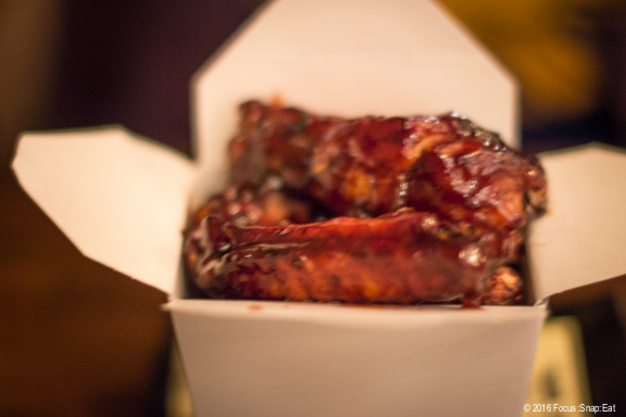 BBQ pork ribs ($8) with tamarind glaze served in a takeout box.