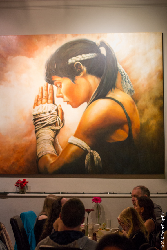 One of the prominent women kick boxing paintings in the dining room.